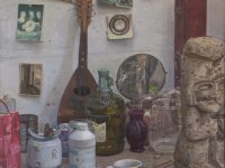 """Studio Still Life 2 (oil on canvas, 25"""" x 25"""", 1995) Manny Cosentino, Paintings. Still life of various objects and brick a brack on a counter in the artist's studio. Items include an old mandolin, old postcards, a broken teapot, a dried butterfly, a bottle of olive oil and an Aztec sculpture."""