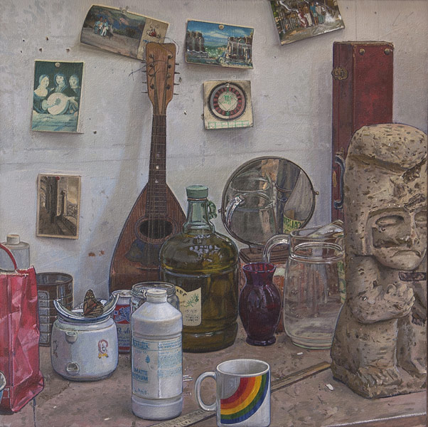 Studio Still Life 2. Oil painting, still life, more detritus in the studio: old postcards, an old mandolin and a red leather clarinet case line the wall. Various vessels, vases, cups, a can, a broken tea pot and a gallon of olive oil on the table. A faux Aztec sculpture on the right edge of the composition. Hyperreal execution. © Manny Cosentino, 1995.