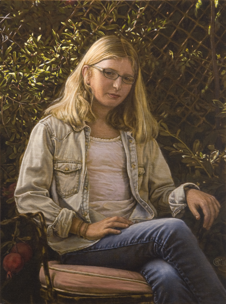 Portrait of a young girl sitting outside with pomegranates growing in the bushes behind her. ©Manny Cosentino